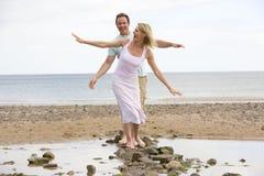 Pares en la playa que recorre en piedras y la sonrisa Fotos de archivo libres de regalías