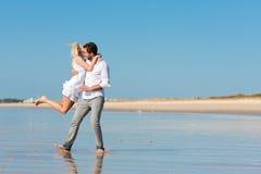 Pares en la playa que se ejecuta en futuro glorioso Foto de archivo