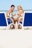 Pares en la playa que se relaja en sillas y Champán de consumición Fotos de archivo libres de regalías