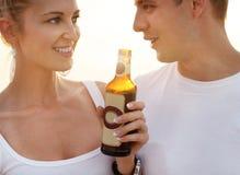 Pares en la playa que tiene partido, bebiendo y divirtiéndose en Fotografía de archivo libre de regalías