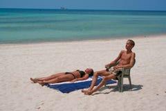 Pares en la playa que toma el sol Foto de archivo libre de regalías