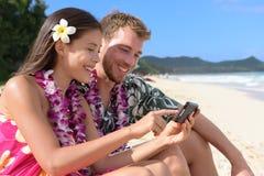 Pares en la playa usando el teléfono elegante en Hawaii Fotos de archivo libres de regalías
