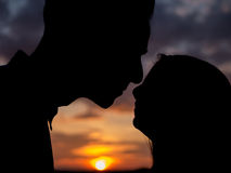Pares en la puesta del sol antes de besarse Imagen de archivo