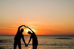 Pares en la puesta del sol de oro en la playa imagenes de archivo