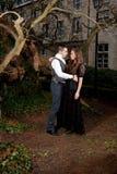 Pares en la ropa victoriana que abraza en el parque imagenes de archivo