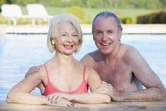 Pares en la sonrisa al aire libre de la piscina Fotografía de archivo libre de regalías