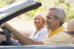 Pares en la sonrisa convertible del coche Fotos de archivo libres de regalías