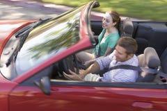 Pares en la sonrisa convertible del coche Fotografía de archivo
