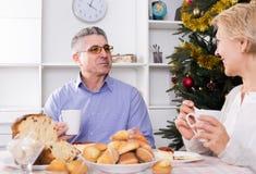 Pares en la tabla que celebra la Navidad y el Año Nuevo en casa Imagen de archivo libre de regalías