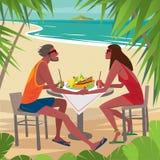 Pares en la tabla que come el desayuno en la playa Fotos de archivo libres de regalías