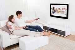 Pares en la televisión de observación de la sala de estar Foto de archivo