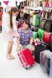 Pares en la tienda que elige la maleta Fotografía de archivo libre de regalías