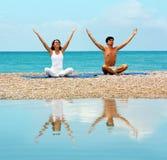 Pares en la yoga practicante de la playa Foto de archivo
