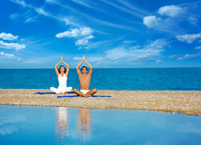Pares en la yoga practicante de la playa fotos de archivo libres de regalías