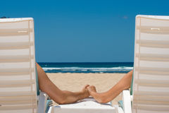 Pares en las sillas de playa que llevan a cabo las manos Imagenes de archivo