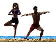 Pares en los exercices de la yoga de la playa Foto de archivo libre de regalías