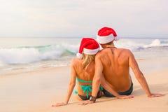 Pares en los sombreros de Papá Noel que se sientan en la playa Foto de archivo libre de regalías