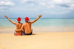 pares en los sombreros rojos de Papá Noel en la playa tropical fotografía de archivo libre de regalías