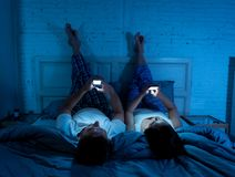 Pares en los teléfonos móviles en cama tarde en la noche que disfruta de la red, de juegos y de la conexión a internet sociales imagen de archivo libre de regalías