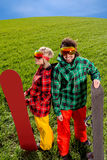 Pares en los trajes de esquí y los vidrios de sol que se colocan de lado a lado con s Imagenes de archivo