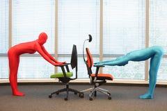 Pares en los trajes elásticos del cuerpo completo que ejercitan con las sillas en oficina Fotos de archivo