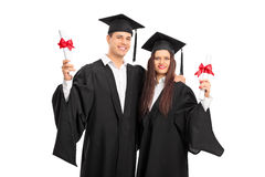 Pares en los vestidos de la graduación que presentan con los diplomas Foto de archivo
