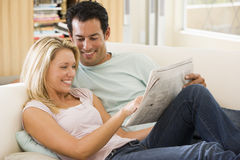 Pares en periódico de la lectura de la sala de estar Imagen de archivo