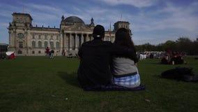 Pares en prado delante del edificio de Reichstag, Berlín, Alemania almacen de video