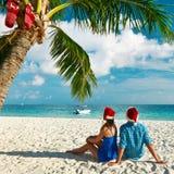 Pares en ropa azul en una playa en la Navidad Fotos de archivo