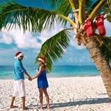 Pares en ropa azul en una playa en la Navidad Foto de archivo