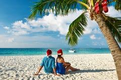 Pares en ropa azul en una playa en la Navidad Imágenes de archivo libres de regalías