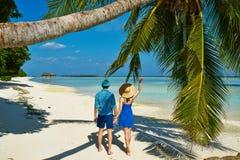 Pares en ropa azul en una playa en Maldivas Imagen de archivo libre de regalías