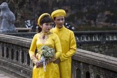 Pares en ropa tradicional en Royal Palace en tonalidad, VI de la boda Imagenes de archivo