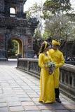 Pares en ropa tradicional en Royal Palace en tonalidad, VI de la boda Imagen de archivo