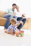 Pares en sala de estar con el bebé Fotos de archivo libres de regalías