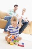 Pares en sala de estar con el bebé Imágenes de archivo libres de regalías