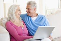 Pares en sala de estar con la sonrisa de la computadora portátil Imágenes de archivo libres de regalías