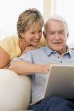 Pares en sala de estar con la sonrisa de la computadora portátil Foto de archivo libre de regalías