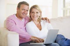 Pares en sala de estar usando la computadora portátil foto de archivo libre de regalías