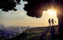 Pares en silueta en la opinión de la ciudad de la puesta del sol fotos de archivo
