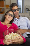 Pares en Sofa Watching TV que lleva los vidrios 3D que comen las palomitas Fotos de archivo