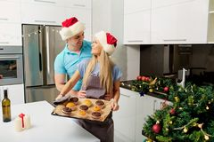 Pares en sombreros del ` s de Papá Noel en la cocina el día de la Navidad Foto de archivo