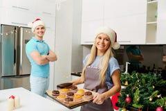 Pares en sombreros del ` s de Papá Noel en la cocina el día de la Navidad Fotografía de archivo