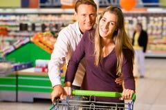 Pares en supermercado con el carro de compras Fotografía de archivo libre de regalías