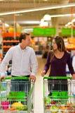 Pares en supermercado con el carro de compras Foto de archivo libre de regalías