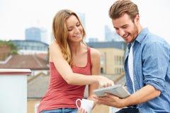 Pares en terraza del tejado usando la tableta de Digitaces Foto de archivo libre de regalías