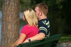 Pares en un banco de parque Imagen de archivo libre de regalías