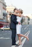 Pares en un beso en el camino Recienes casados que se besan en la tira de división Tema de la boda Imagenes de archivo