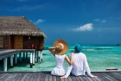 Pares en un embarcadero de la playa en Maldivas foto de archivo libre de regalías