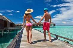 Pares en un embarcadero de la playa en Maldivas Fotos de archivo libres de regalías